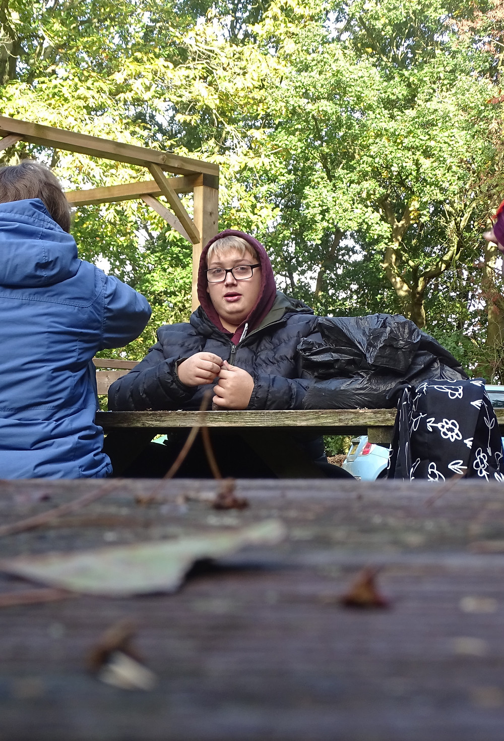 A student sat on a picnic table in the woods.