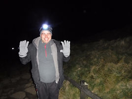 Alex taking part in a night walk in the Peak District. He has a torch on his head and is wrapped up for the cold.