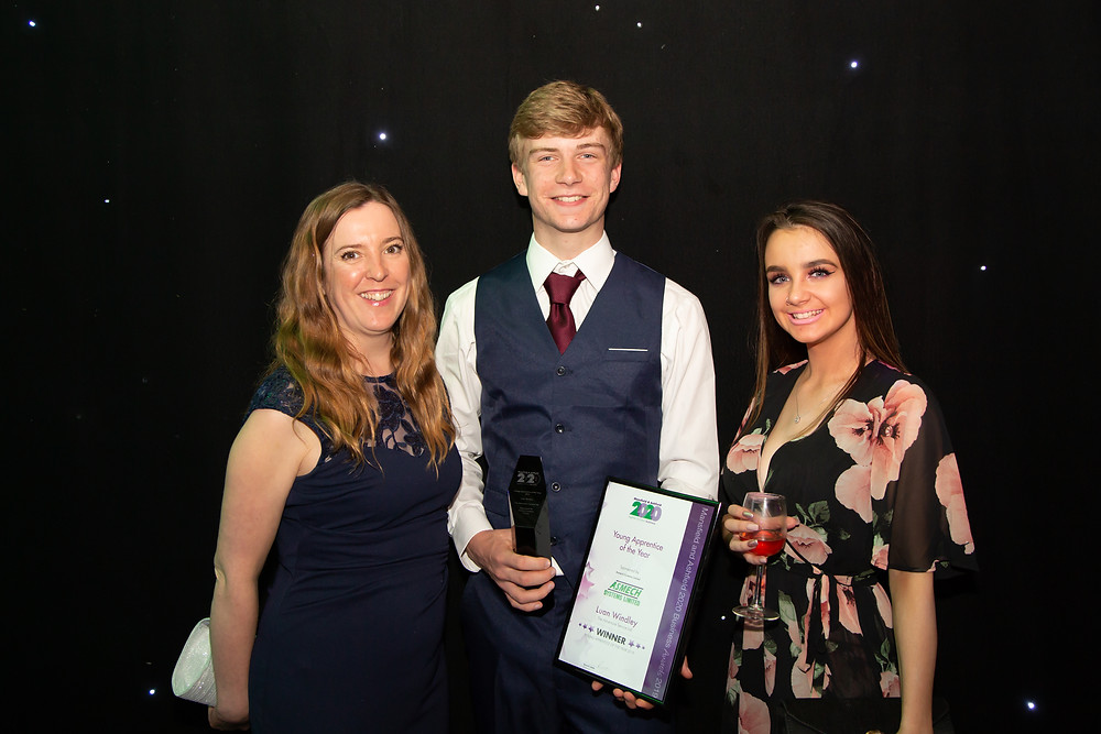 Two apprentices with their boss after winning Apprentice of the Year Award.