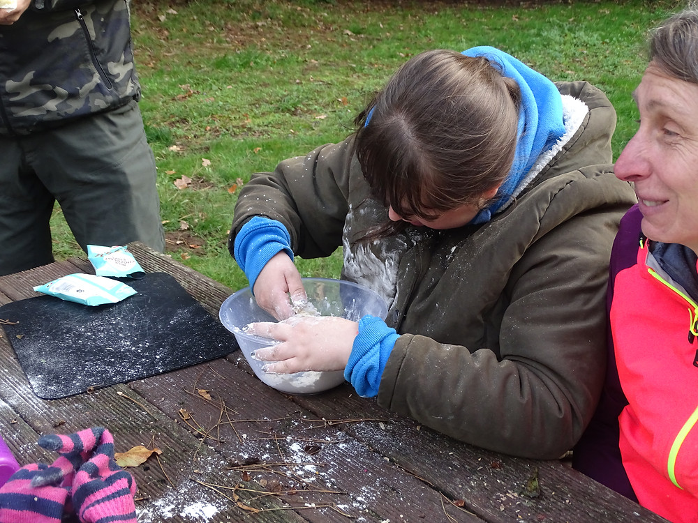 A student covered in flour enjoying making some bread dough.