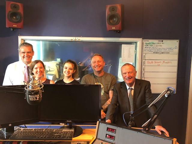 Five people in a radio studio.