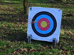 An archery board with several arrows in