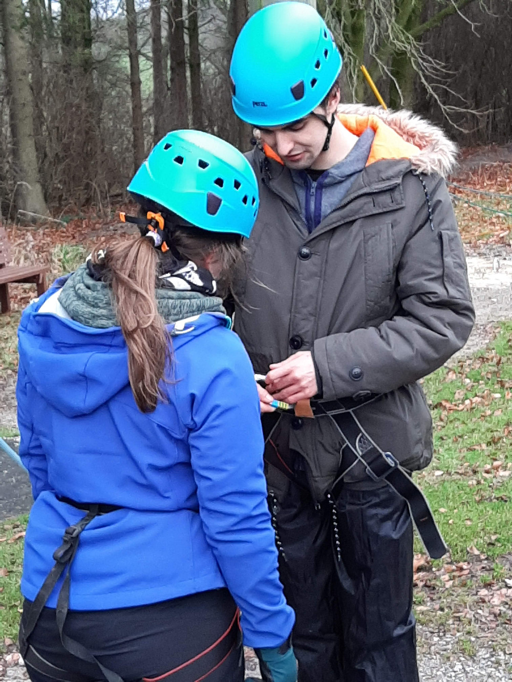 A female outdoor instructor strapping a service user into a harness.