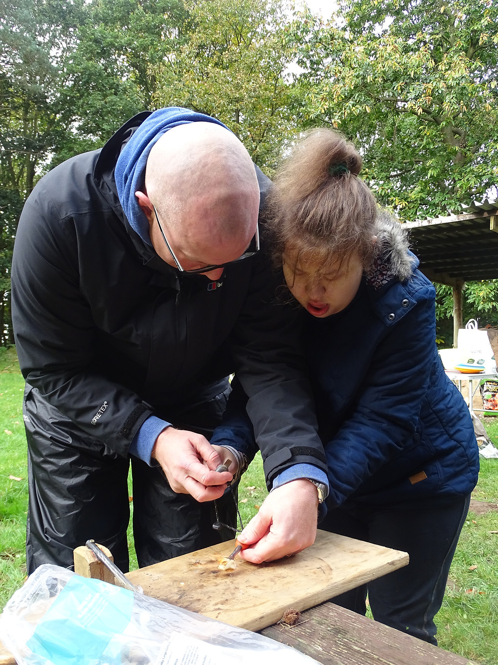 A teacher and a student setting fire to some cotton wool with a fire steel.