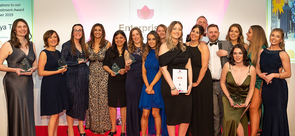 A group of people on a stage holding awards, at the East Midlands Chamber Enterprising Women Awards.