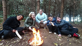 A group of schoolchildren at Oxclose Woods around a campfire