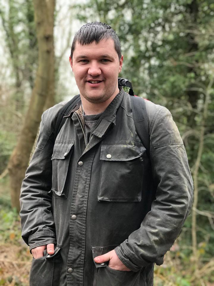 Service user posing for a portrait photograph, in some woodland, while on a walk.
