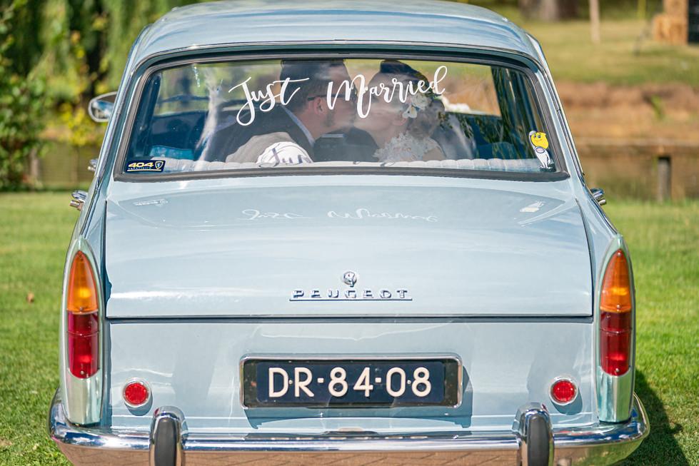 Trouwauto en bruidspaar op de achterbank