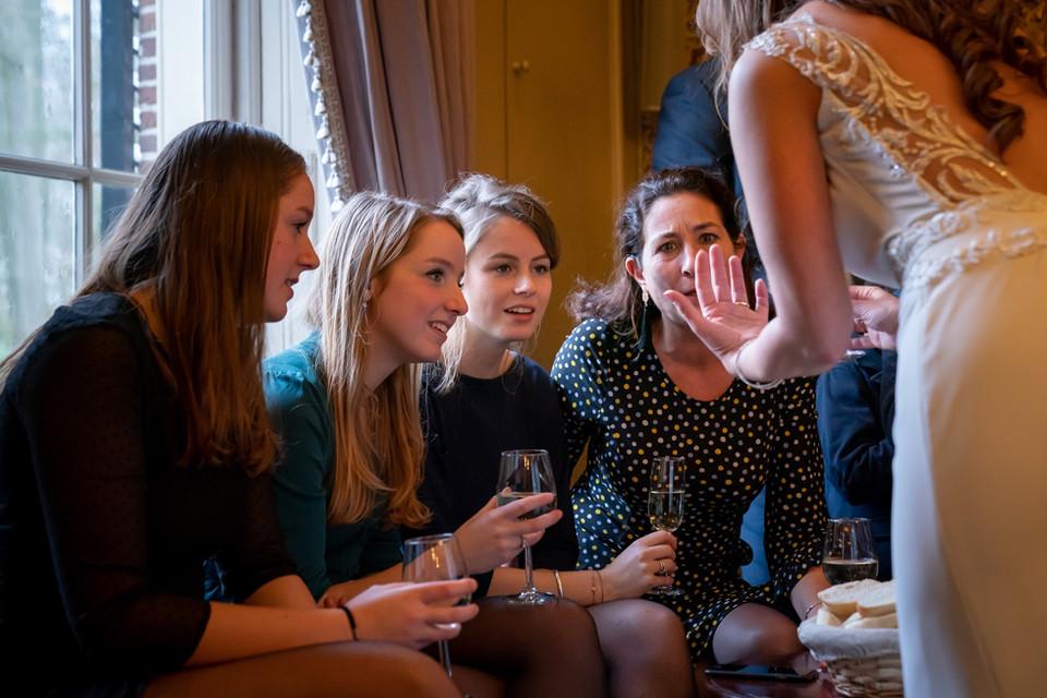 Bruid laat trouwring zien aan gasten