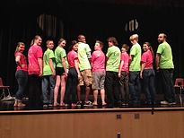 student performers onstage colorful shirts