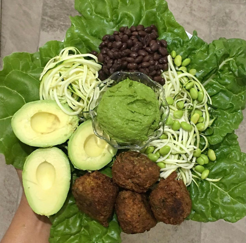 Fried falafel with avocado, zucchini noodles, black beans, edamame, basil-kale pesto on a bed of greens