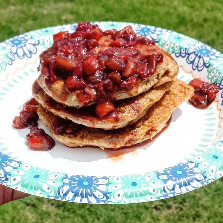 Fluffy whole wheat pancakes topped with warm strawberry compote