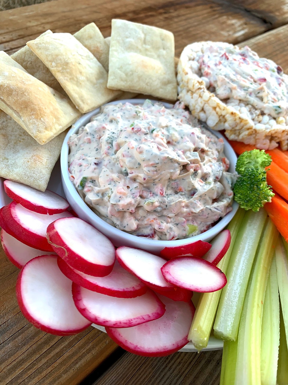 Vegan vegetable cream cheese with homemade crackers, rice cakes and fresh vegetables