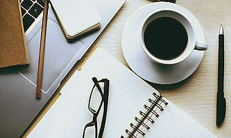 Image of desk with office equipment and coffee cup