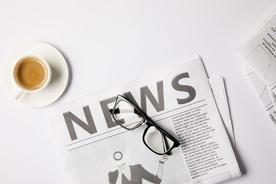 flat-lay-with-eyeglasses-cup-of-coffee-and-newspaper-press-release-.jpg