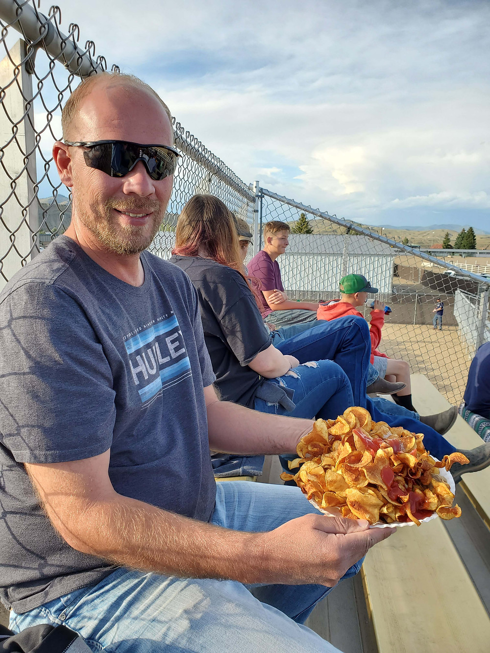 Man showing off fresh warm potato chips.