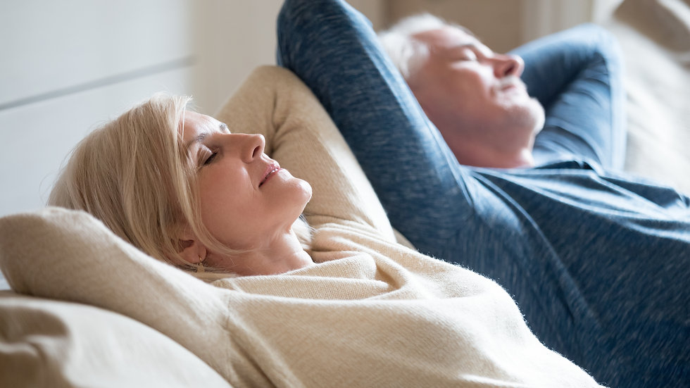 Senior aged couple relaxing on comfortab