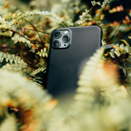 black-smartphone-surrounded-with-plants-