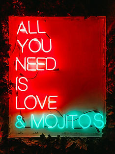 A neon sign 'All You Need Is Love' in red and '& Mojitos' in a mint green. On a red background with leaves around the outside of the frame