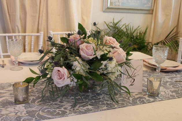 Pink flower on sweetheart table Thisle flower bar