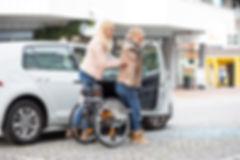 Eine Persönliche Assistentin hilft einer Rollstuhlfahrerin beim Einstieg ins Auto.