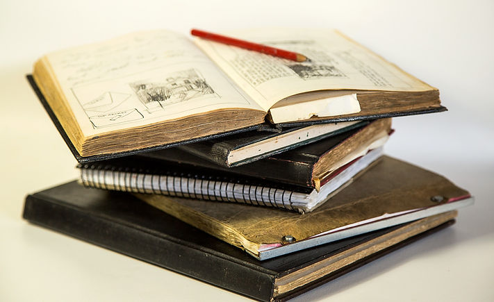 stack of sketch books, journals and diaries