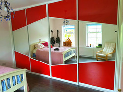 customised red glass and mirror angled sliding doors with a white frame fitted by sliding wardrobes