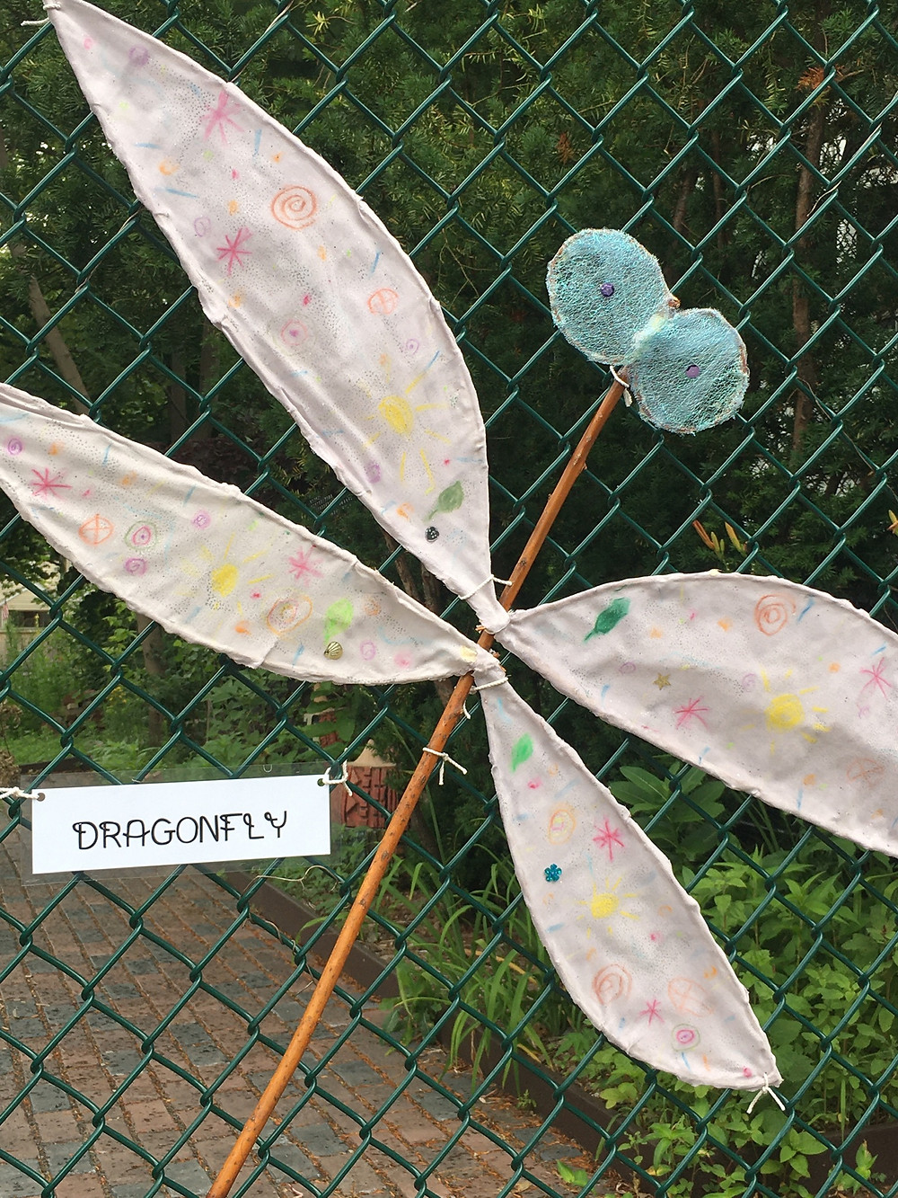 A willow branch dragonfly attached to the Growing Center fence.