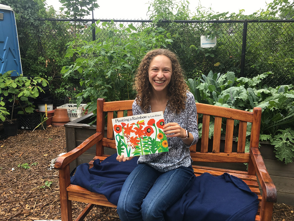 """Becca sitting on a bench in the raised bed section of the garden, holding the book, """"Planting a Rainbow."""""""