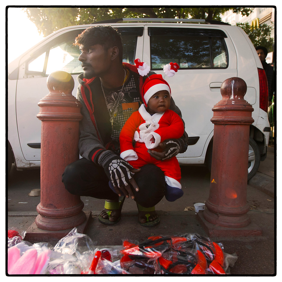 Seller awaits customers with his child as son sets.