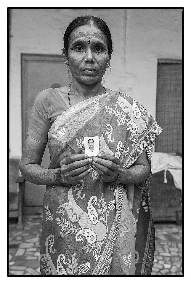 Laxshmi Devi with photo of her deceased husband M. Nagesh, tenant farmer, Jainath village Andhra Pradesh. Nagesh committed suicide over an unpaid loan of $ 5900.