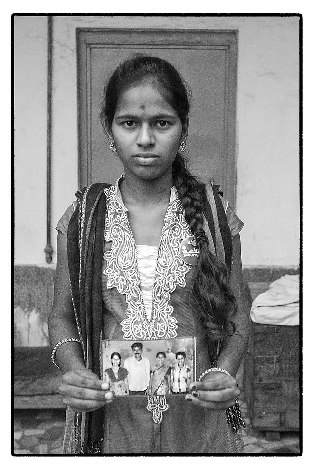 18 year old Manisha with photo of her family, Gaurya Palle village, Telengana. Her parents, bothe tenant farmers, committed suicide and she has dropped out of school to support herself and her younger brother seen in the family photo.
