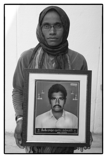 Madhavi with photo of her deceased husband D. Mahendar – a tenant farmer who was unable to repay a farm loan of $14,325 and committed suicide.