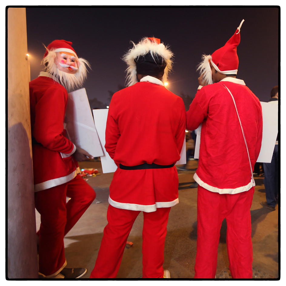 Men dressed as Santa Claus to promote a kids wear store.