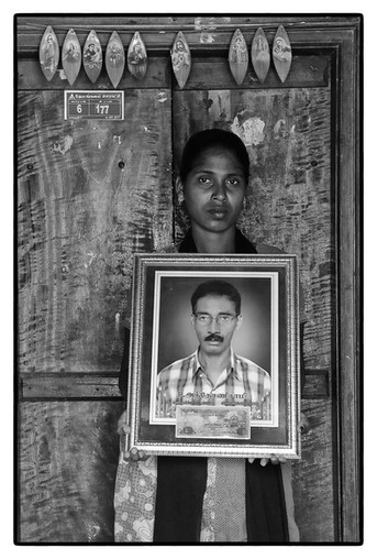 V. Mary with photo of her deceased father Anthony Swamy, a tenant farmer in Tamil Nadu.