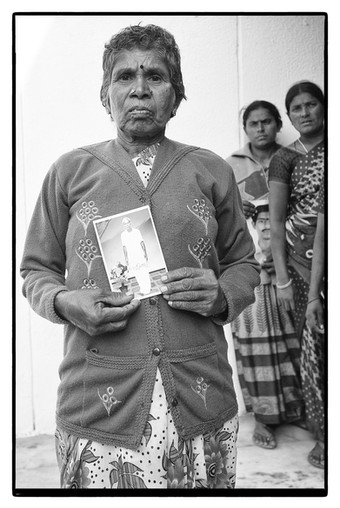 Ramanamma with photo of her husband A. Lakshmaiah – a farmer who committed suicide over an unpaid $18,623 loan, India. The husbands of the three women behind her also committed suicide.