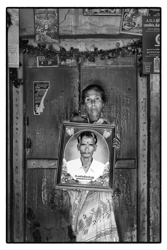 A. Mary with photo of her tenant farmer husband S. M. Kanu, Ookur village, Tamil Nadu. Debt-stressed Kanu 'died of a heart attack' at the age of 42.