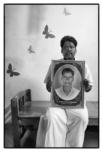 S. Ramesh with photo of his older brother S. Kaiyan Sundaram both farmers in Tamil Nadu. Sundaram died 'due to heart attack' caused by stress of unpaid loans.