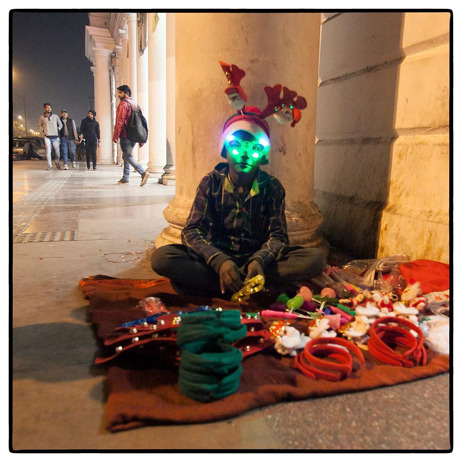 Teenage seller  with lights mask, Santa cap and antlers.