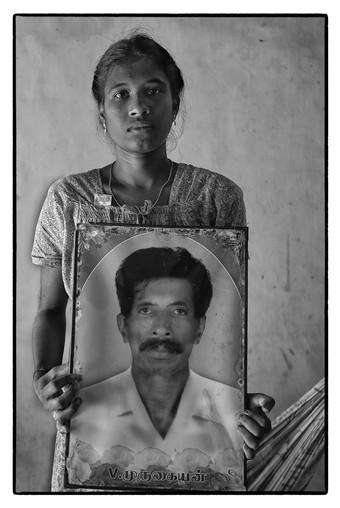 Nitya with photo of her father V. Murugan, Thalinagar village, Tamil Nadu.  Murugan, a debt-stressed tenant  farmer committed suicide.
