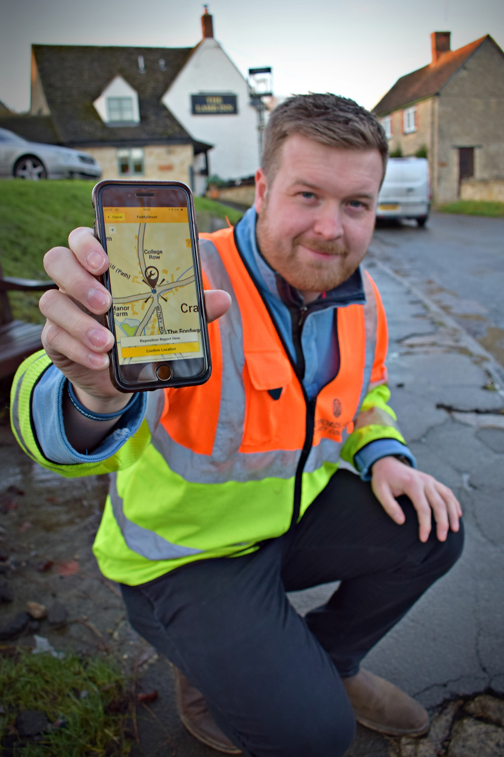 Cllr Walker with the FixMyStreet App on his phone.