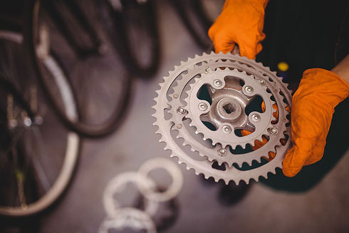 mechanic-holding-bicycle-gear.jpg