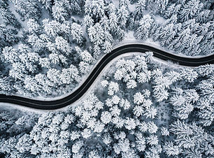 Curvy windy road in snow covered forest,