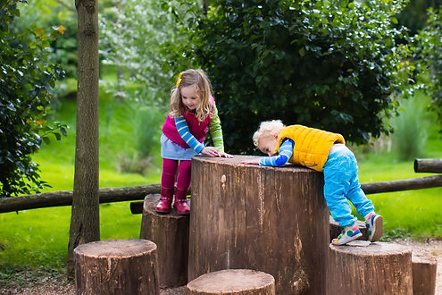 Little boy and girl climbing on a wooden