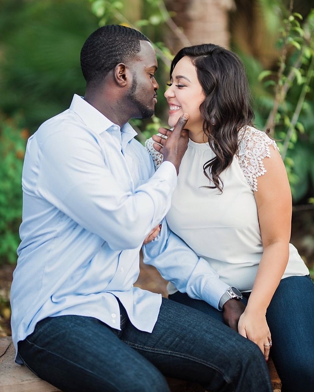 Black man and hispanic woman smiling and holding each other while sitting on a bench under trees