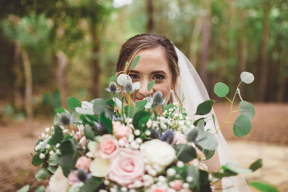 Bride holds her wedding bouquet up, slightly blocking her face