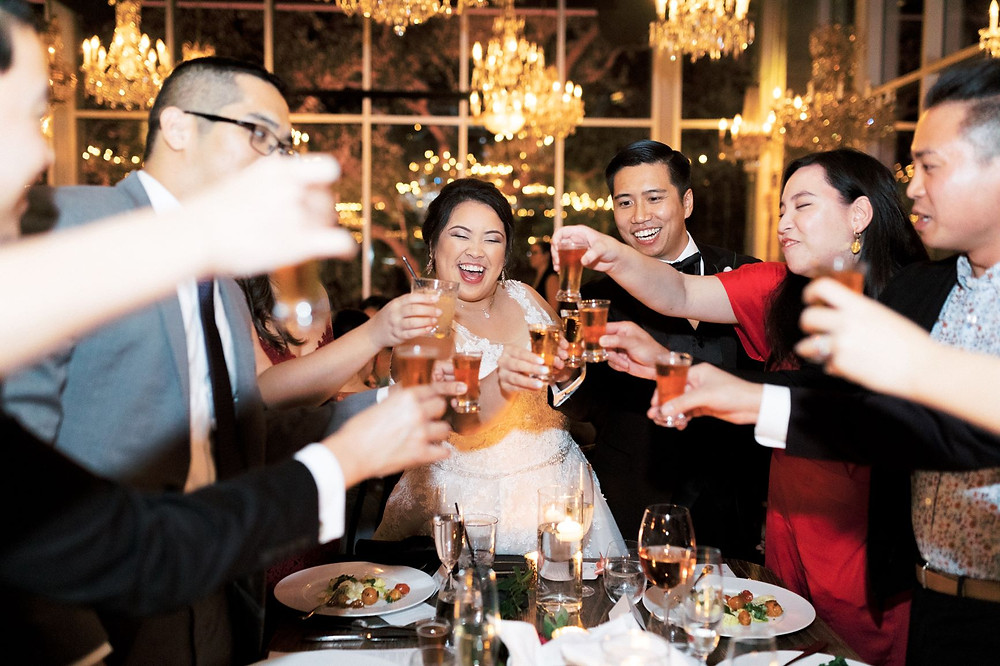 Bride and groom toasting shots with guests at asian wedding