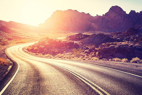 Vintage toned scenic desert road at suns