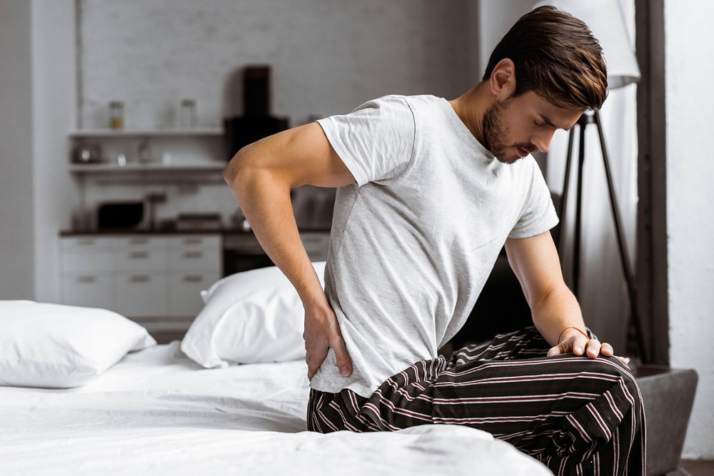 Young-Man-In-Pyjamas-With-Back-Pain