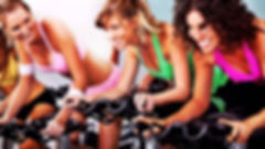 Three women on indoor bikes